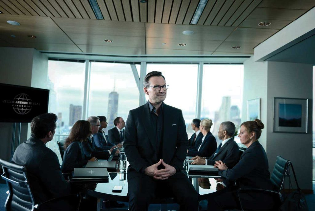 Christian-Slater-standing-in-a-corporate-boardroom-
